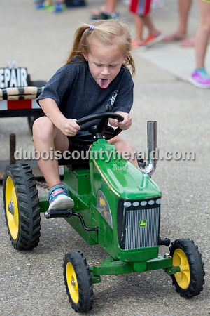 Sarah Shaw/The Herald Madelyn Berg stuck her tongue out while pedaling in the kiddie tractor pull during the St. Anthony Firemen's Fest in St. Anthony on Saturday.
