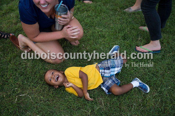Allen Ondiek of Ireland, 2, laughed after being tickled by his second cousin Nicole Green of Ireland, left, during the Ireland Bicentennial celebration Friday evening. Sarah Ann Jump/The Herald