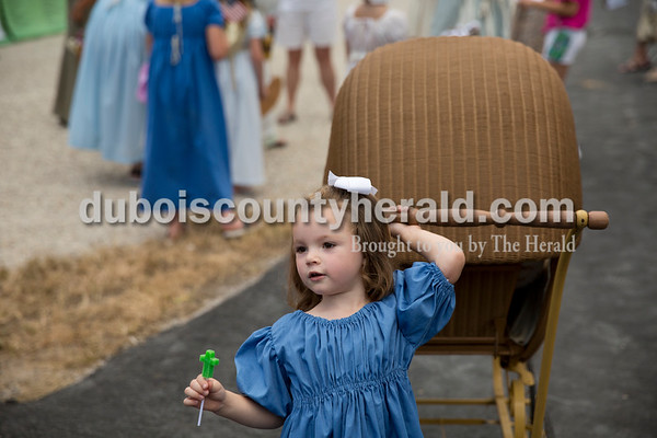 Harper Showalter of Jasper, 3, hung on to a baby carriage that once belonged to her great-great-great-grandmother before the Old Irish Fashion Show during the Ireland Bicentennial celebration Friday evening. Sarah Ann Jump/The Herald