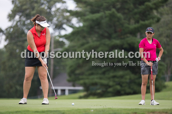 Forest Park's Skyla McKim putted while New Albany's Stevie Roth looked on during the Wildcat Invitational at Buffalo Trace Golf Course in Jasper on Saturday.  Sarah Shaw/The Herald