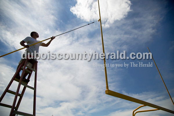 Sarah Shaw/The Herald Tony Benton of Jasper painted the goal posts at Jerry Brewer Alumni Stadium in Jasper on Tuesday. Jasper's first home game will be next Friday against Boonville High School.