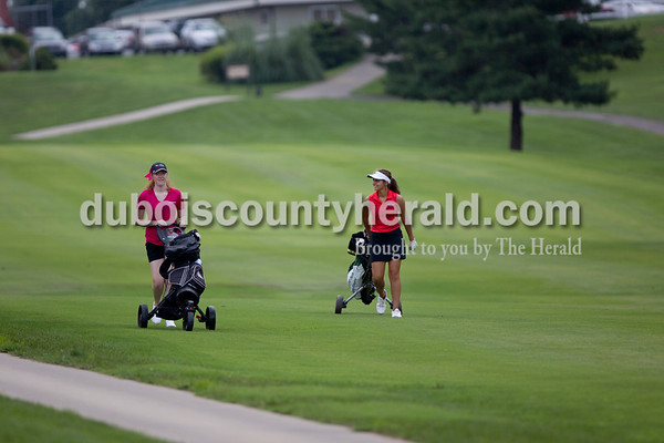 New Albany's Erin Bell and Forest Park's Emily Nord talked while walking along the fairway during the Wildcat Invitational at Buffalo Trace Golf Course in Jasper on Saturday.  Sarah Shaw/The Herald