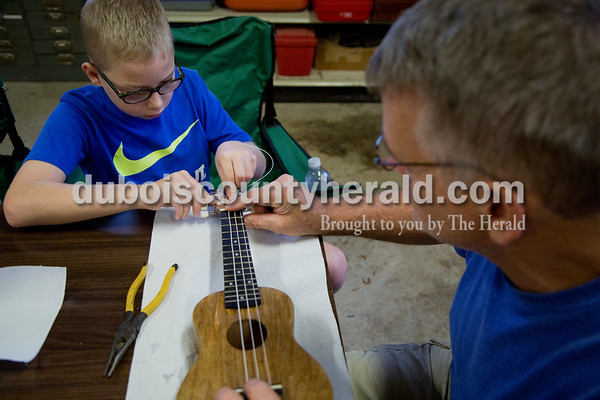 Sarah Shaw/The Herald Mason Tobin of Ferdinand, 10, strung his ukulele with help from Doug Abell of Ferdinand during the Project A.C.O.R.N ukulele-making workshop in Ferdinand on Saturday. Inspired by the Ferdinand Folk Festival, Project A.C.O.R.N., standing for Art, Community, Originality, Rhythm, and Nature, is a new community outreach group in Ferdinand that strives to provide learning opportunities for youth and amateurs of all ages in the areas of music, art, environment, and wellness. The group hosted a three-week ukulele-making workshop for both children and adults. Over 30 ukuleles were built during the workshops. The group hopes to offer a ukulele class in the fall so that participants can learn to play their new instruments.