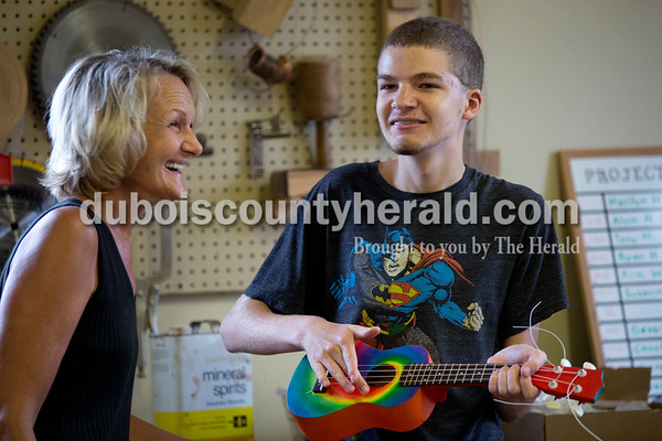 Sarah Shaw/The Herald Project A.C.O.R.N. co-chair Deb Abell of Ferdinand celebrated after Guy Austin of Birdseye, 15, strummed his ukulele for the first time during the Project A.C.O.R.N ukulele-making workshop in Ferdinand on Saturday. Inspired by the Ferdinand Folk Festival, Project A.C.O.R.N., standing for Art, Community, Originality, Rhythm, and Nature, is a new community outreach group in Ferdinand that strives to provide learning opportunities for youth and amateurs of all ages in the areas of music, art, environment, and wellness. The group hosted a three-week ukulele-making workshop for both children and adults. Over 30 ukuleles were built during the workshops. The group hopes to offer a ukulele class in the fall so that participants can learn to play their new instruments.