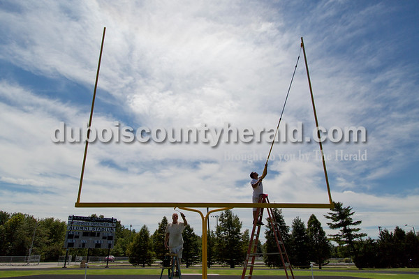 Sarah Shaw/The Herald Doug Schmitt and Tony Benton, both of Jasper, painted the goal posts at Jerry Brewer Alumni Stadium in Jasper on Tuesday. They wanted to finish painting before the forecasted thunderstorms this week. Jasper's first home game will be next Friday against Boonville High School.