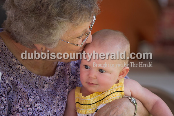 """Sarah Shaw/The Herald Charlene Andry of Birdseye kissed her 5-month-old granddaughter Leah during the town of Birdseye's annual picnic at Birdseye Park on Saturday. """"You look so pretty in your Birdseye Yellow Jacket colored dressed,"""" Andry cooed to Leah. Birdseye High School, which merged with Ferdinand High School to form Forest Park High School in 1971, had the yellow jackets as their mascot."""