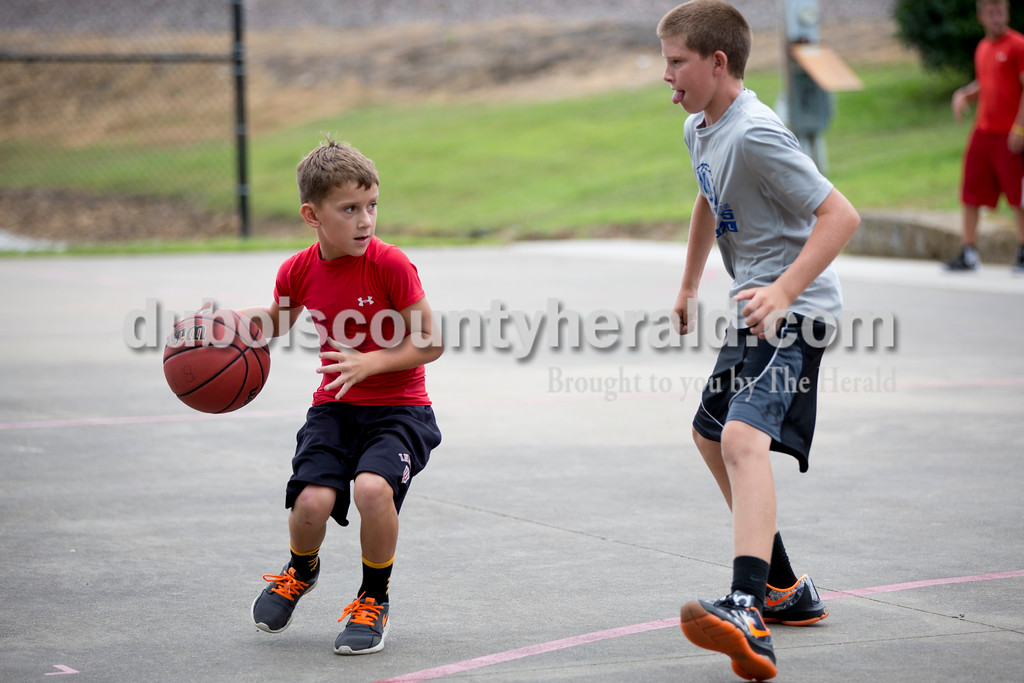 Sarah Shaw/The Herald<br /> Jared Burger of Ferdinand, 8, dribbled past Aden Thewes of Celestine, 12, during the 3-on-3 basketball tournament at the town of Birdseye's annual picnic at Birdseye Park on Saturday.