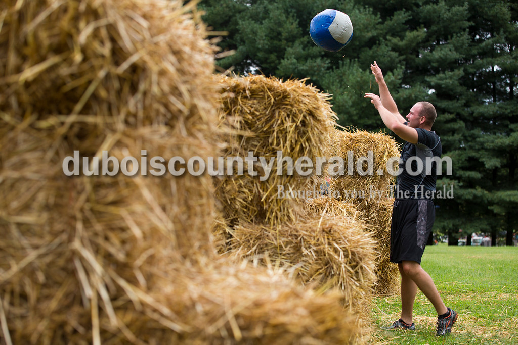 Kurt Schroering of Jasper threw a twenty-pound medicine ball over a stack of hay bales twenty times during the Ireland's Fittest Contest at the Ireland Bicentennial celebration on Saturday. Sarah Ann Jump/The Herald