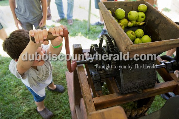 Josh Layman of Ireland, 5, cranked an apple press to make juice as part of the heirloom demonstrations during the Ireland Bicentennial celebration on Saturday. Sarah Ann Jump/The Herald