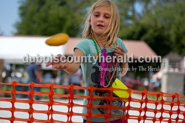 Sarah Shaw/The Herald Alexis Berg of Ferdinand, 6, tossed beanbags while playing a carnival game during the town of Birdseye's annual picnic at Birdseye Park on Saturday.