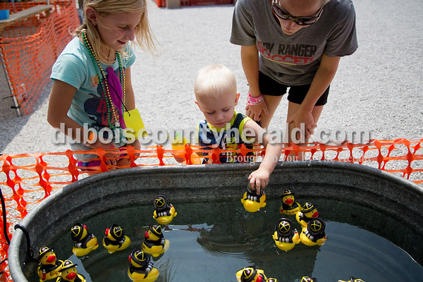 Sarah Shaw/The Herald Carter Schepers of Birdseye, 1, selected a rubber duck while playing a carnival game with Alexis Berg of Ferdinand, 6, and Erika Gehlhausen of Schnellville during the town of Birdseye's annual picnic at Birdseye Park on Saturday.