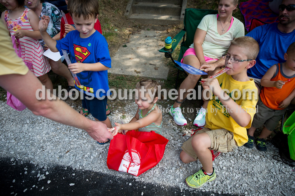 Olivia DeSchamp of Jasper, 5, center, received a piece of candy as Alexander Nord of Jasper, 5, left, looked on and Olivia's brother Austin, 10, right, ate a freeze pop during the Ireland Bicentennial parade on Sunday. Sarah Ann Jump/The Herald