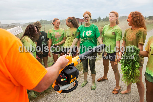 Erik Dismore of Jasper used a leaf blower to clean the colored corn starch off of Color Me Crazy 5k volunteers, from left, Samantha Capehart, Shelby Mullen, Emily Heim, 14, Reagan Egbert, 14, Mallory Alles, Taylor Greulich, 15, and Maddie Vernon, 14, all of Jasper, after the race during the Ireland Bicentennial celebration on Saturday. Sarah Ann Jump/The Herald