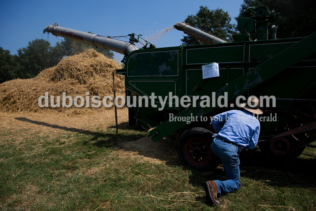 John Kern of Mariah Hill inspected a 1940 Oliver thresher owned by Bob Demuth of Ferdinand to see what needed to be fixed during the Ireland Bicentennial celebration on Saturday. Sarah Ann Jump/The Herald