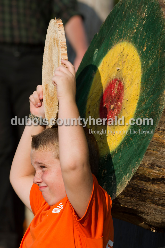 """Owen Gehlhausen of Jasper, 8, held a piece of wood over his head as the lumberjacks jokingly told him they were going to throw an axe at it during the Olympics of the Forest show at the Ireland Bicentennial celebration on Saturday. Owen said he was """"kinda"""" nervous but did what was asked. Sarah Ann Jump/The Herald"""