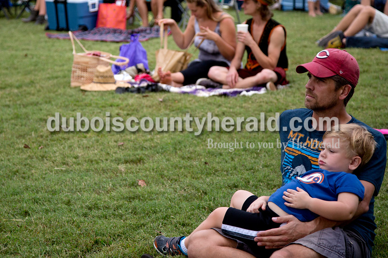 Sarah Shaw/The Herald<br /> Charlie Miller of Princeton, 3, sat in his father's lap while watching music performances during the Ferdinand Folk Festival in Ferdinand on Saturday.