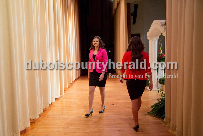 Sarah Shaw/The Herald<br /> Louisa Nino of Huntingburg, 17, left, smiled as she passed Lauren Meyer of Huntingburg, 17, while exiting the stage during the professional wear portion of the Miss Herbstfest pageant at Southridge High School in Huntingburg on Sunday.