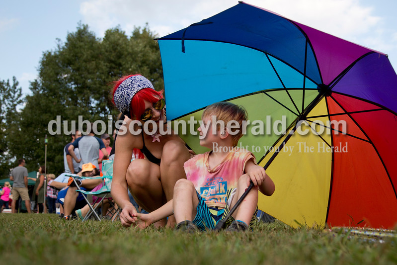 Sarah Shaw/The Herald<br /> Joseph Shiver of Jasper, 6, chatted with his mother, Allison Doane, from his spot in the shade during the Ferdinand Folk Festival in Ferdinand on Saturday.