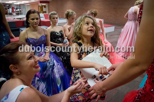 Sarah Shaw/The Herald Elizabeth Brinkman of Ferdinand, 20, bottom left, passed a program to Bailey Barrett of Huntingburg, 18, for her to sign after Abigail Flamion of Huntingburg, 6, center asked for autographs from all of the contestants during the pageant at Southridge High School in Huntingburg on Sunday. Flamion's mother is on the Herbstfest committee.