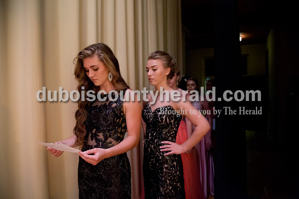 Sarah Shaw/The Herald Montana Jones of Huntingburg, 16, right, read the list of potential quesionts over the shoulder of Lauren Meyer of Huntingburg, 17, during the pageant at Southridge High School in Huntingburg on Sunday.