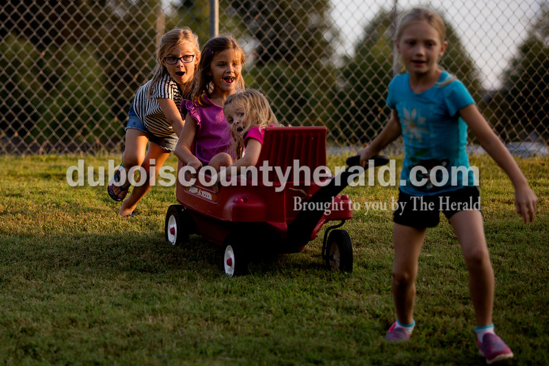 Sarah Shaw/The Herald<br /> Abby Eaton of Columbus, 5, left, pushed her sisters Ellie, 7, and Sophia, 4, in a wagon pulled by Nora Welp of Ferdinand, 8, during the Ferdinand Folk Festival in Ferdinand on Saturday. The Eaton sisters were in Ferdinand staying with Nora and her family.