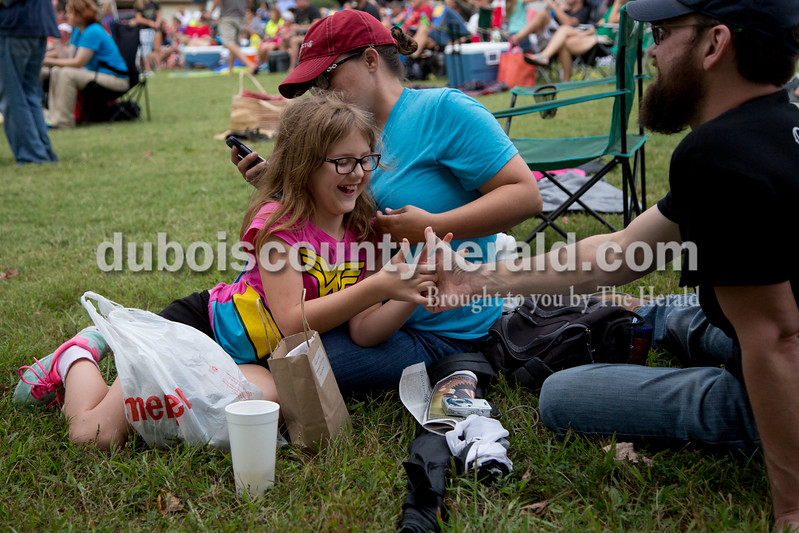 Sarah Shaw/The Herald<br /> Eliza Culp of Mount Carmel, Ill., 10, used her mother, Pam, as a lounger, while thumb wrestling with her father, Lyle, during the Ferdinand Folk Festival in Ferdinand on Saturday.