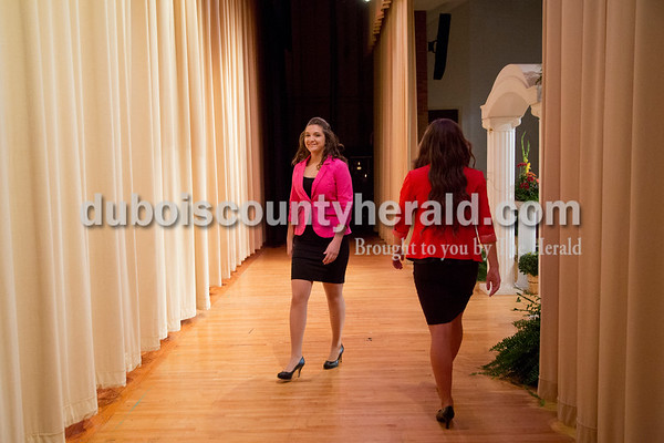 Sarah Shaw/The Herald Louisa Nino of Huntingburg, 17, left, smiled as she passed Lauren Meyer of Huntingburg, 17, while exiting the stage during the professional wear portion of the Miss Herbstfest pageant at Southridge High School in Huntingburg on Sunday.