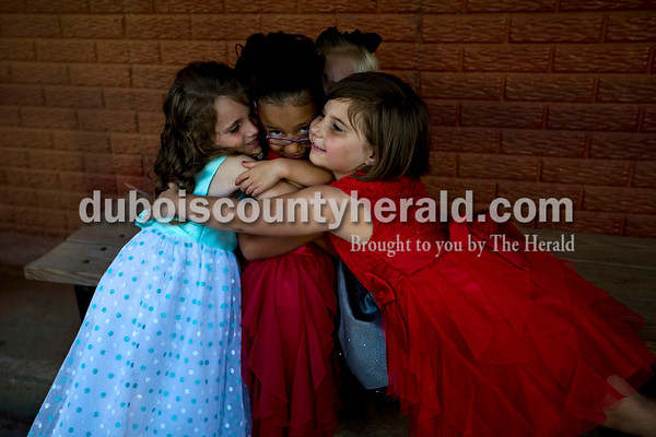 Kennedy Poehlein, 6, left, Sophia DeKemper, 5, back, both of Huntingburg, and Jaden Hopf of Schnellville, 6, right, embraced their fellow contestant Jazmin Dubon of Huntingburg, 6, as they waited to go onstage during the Little Miss Herbstfest pageant Friday night in Huntingburg.  Alisha Jucevic/The Herald