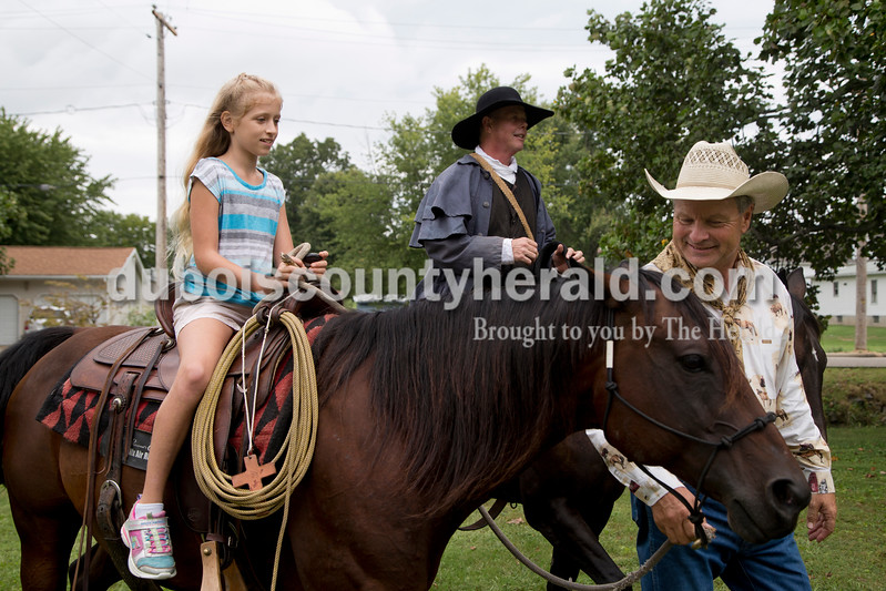 Sarah Shaw/The Herald<br /> Calvin Barfield of Conway, S.C., right, gave Ayla Romans of Rockport, 10, a ride on Honey, an American quarter horse, while Mike Mulligan of Waxhaw, N.C., rode alongside them during the Cowboys for Christ event at Christ Community Fellowship Church in Huntingburg on Saturday. Barfield and Mulligan travelled to Huntingburg with their horses, Honey and Sassy, to give rides to kids and preach about Jesus.