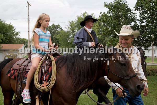 Sarah Shaw/The Herald Calvin Barfield of Conway, S.C., right, gave Ayla Romans of Rockport, 10, a ride on Honey, an American quarter horse, while Mike Mulligan of Waxhaw, N.C., rode alongside them during the Cowboys for Christ event at Christ Community Fellowship Church in Huntingburg on Saturday. Barfield and Mulligan travelled to Huntingburg with their horses, Honey and Sassy, to give rides to kids and preach about Jesus.