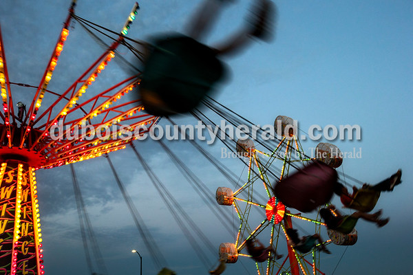 Kids twirled around on the Swinger ride during opening night of Herbstfest on Thursday night in Huntingburg City Park.  Alisha Jucevic/The Herald