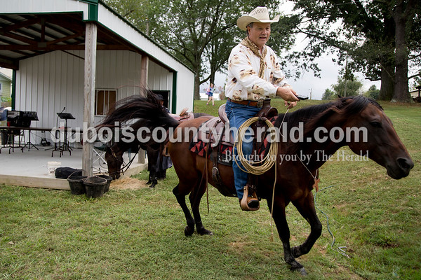 """Sarah Shaw/The Herald Calvin Barfield of Conway, S.C., used a remote to tell his """"remote-controlled horse"""" Honey to go faster during the Cowboys for Christ event at Christ Community Fellowship Church in Huntingburg on Saturday. Barfield is a traveling cowboy preacher who uses his horse to both entertain and share the gospel."""