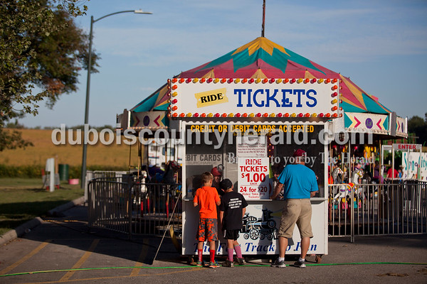 Zander Duncan, 10, left, Mason Fisher, 9, and Kevin Mathies, all of Huntingburg, bought carnival tickets during opening night of Herbstfest on Thursday night in Huntingburg City Park.   Alisha Jucevic/The Herald