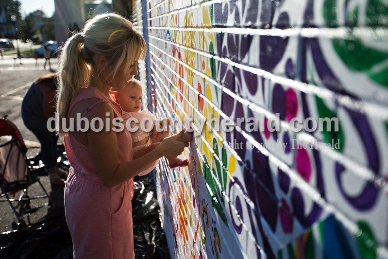 Jillian Becher pressed her daughter's foot, Hampton, 10 months, against the the community mural in downtown Jasper to create a footprint during the community paint night on Wednesday evening. <br /> Alisha Jucevic/The Herald