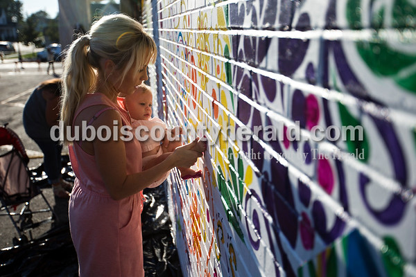 Jillian Becher pressed her daughter's foot, Hampton, 10 months, against the the community mural in downtown Jasper to create a footprint during the community paint night on Wednesday evening.  Alisha Jucevic/The Herald