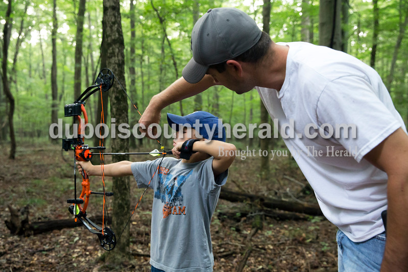 Adam Beck of Celestine helped his son Sam, 7, adjust his peep sight during the 3D target shoot hosted by Patoka Lake Bowhunters at Patoka Lake Archery Range on Sunday, Sept. 18.