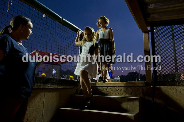 Mya Menke of Holland, 8, and Ayla Hargett of Huntingburg, 10, walked back in the dugout to wait for the final results during the Little Miss and Junior Miss Herbstfest pageant Friday night in Huntingburg.  Alisha Jucevic/The Herald