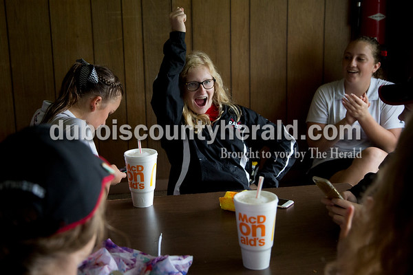 Sarah Shaw/The Herald Southridge's Megan Buechler, center, practiced her cheerleading moves while Morgan Stapleton, right, sang the school song while the team killed time during the weather delay during sectionals at Buffalo Trace Golf Course in Jasper on Saturday. Buechler is also on the cheerleading team.