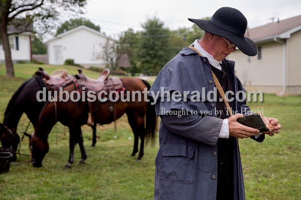 Sarah Shaw/The Herald Mike Mulligan of Waxhaw, N.C., thumbed through his bible before preaching at the Cowboys for Christ event at Christ Community Fellowship Church in Huntingburg on Saturday. Mulligan and Calvin Barfield of Conway, S.C., travelled to Huntingburg with their horses, Honey and Sassy, to give rides to kids and preach about Jesus.