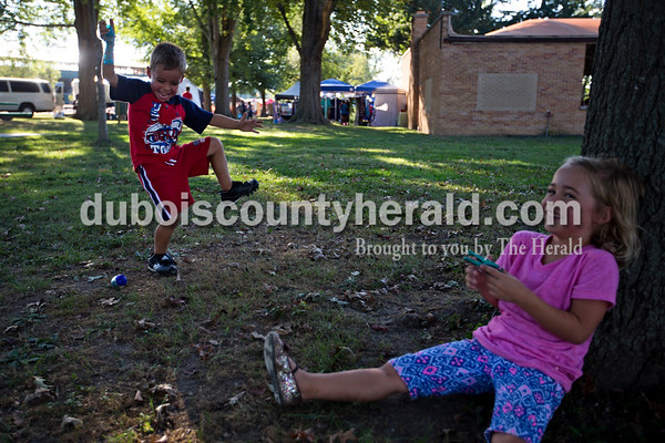 Rylan Hargett, 5, left, and his twin Aubrey, both of Huntingburg, played together during opening night of Herbstfest on Thursday night in Huntingburg City Park. The festival continues throughout the weekend.  Alisha Jucevic/The Herald