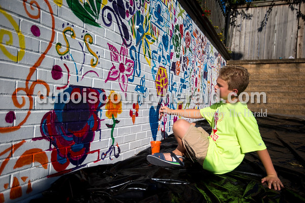 Leo Rasche of Jasper, 11, leaned back to look at his work as he added to the community mural next to Brew on Main St. in downtown Jasper Wednesday evening.   Alisha Jucevic/The Herald