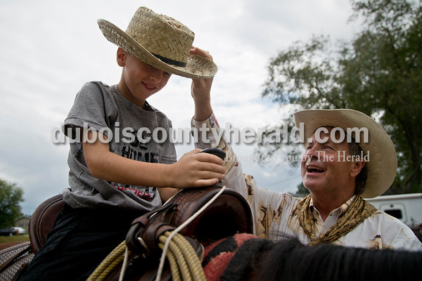 """Sarah Shaw/The Herald Calvin Barfield of Conway, S.C., put a cowboy hat on Brendon Romans of Rockport, 6, during the Cowboys for Christ event at Christ Community Fellowship Church in Huntingburg on Saturday. Barfield and Mike Mulligan of Waxhaw, N.C., travelled to Huntingburg with their horses, Honey and Sassy, to give rides to kids and preach about Jesus. Brendon yelled, """"Yee-haw!"""" after Barfield to him to say a """"cowboy hallelujah."""""""