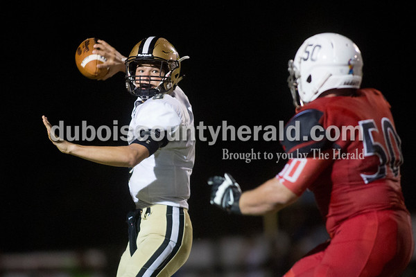 Sarah Shaw/The Herald Jasper's Jacob Ahlbrand prepared to pass the ball as Princeton's Zach Montz came in for the tackle during the game against in Princeton on Friday. Jasper won 35-28.