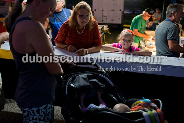 Kat Knies and her granddaughter Alexis Eckert, 8, both of Jasper, said hello to their family friend Maggie Coomer of Jasper and her new baby Georgia, 4, months, during opening night of Herbstfest on Thursday night in Huntingburg City Park. Knies retired from Steinkamp and is now self-employed so she said she loves working at the summer festival to see familiar faces and old customers from the store.  Alisha Jucevic/The Herald