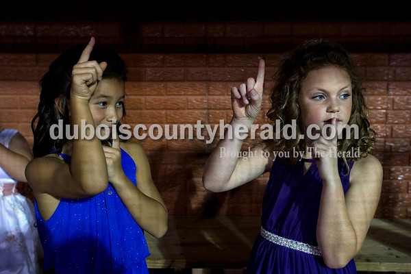 Nicole Fant of Huntingburg, 9, and Emersyn Petry of Holland, 9, held up the silent sign in the dugout as the girls waited for final results during the Little Miss and Junior Miss Herbstfest pageant Friday night in Huntingburg.  Alisha Jucevic/The Herald