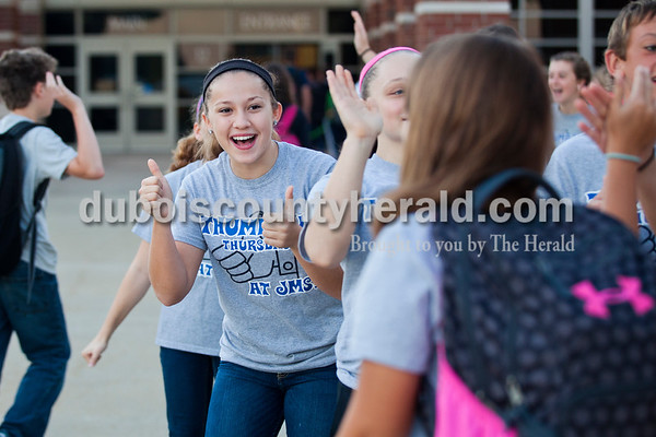 Jasper Middle School eighth grader Kate Kaiser greeted students Thursday morning during Thumbs up Thursday at Jasper Middle School. This is the third year for the weekly event, put on by the students in ROOS club, Respecting Ourselves and Other Students.    Alisha Jucevic/The Herald