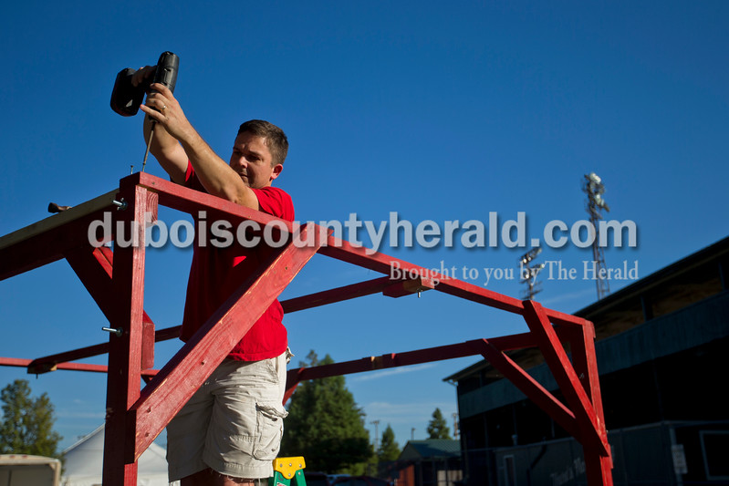 Jason Barnett of Huntingburg put together the Southridge football program booth during Tuesday evening's Herbstfest setup at Huntingburg City Park. The festival begins Thursday evening and continues throughout the weekend. <br /> <br /> Alisha Jucevic/The Herald