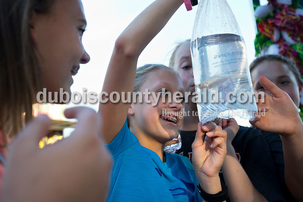 """Loren Fleck of Huntingburg, 12, inspected her new fish after winning a carnival game during opening night of Herbstfest on Thursday night in Huntingburg City Park.  """"I just like pets and fish are the easiest thing,"""" she said. """"They're silent and they don't do anything.""""  Alisha Jucevic/The Herald"""