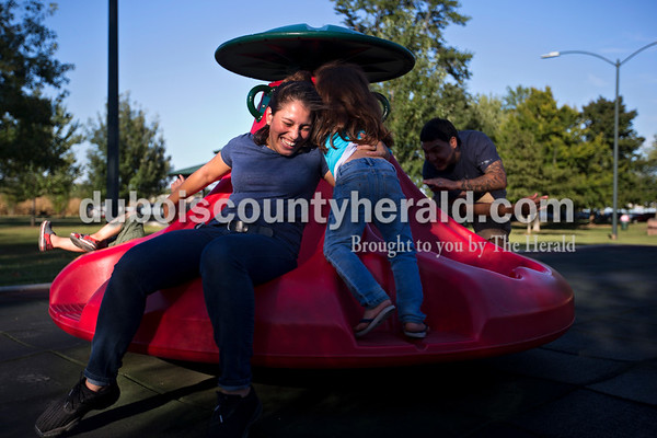 Neisy Hernandez played with her daughter Yolenis, 4, and her husband Irving, right, and their son, Julian, 3, left, all of Huntingburg, during opening night of Herbstfest on Thursday night in Huntingburg City Park.  Alisha Jucevic/The Herald
