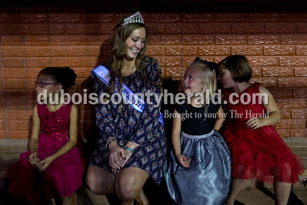 Jazmin Dubon of Huntingburg, 6, left, Herbstfest Queen and Miss Photogenic Bailey Barrett of Huntingburg, 18, Sophia DeKemper of Huntingburg, 5, and Jaden Hopf of Schnellville, 6, sat together in the League Stadium dugout as they waited for results in the Little Miss and Junior Miss Herbstfest pageant Friday night in Huntingburg.  Alisha Jucevic/The Herald